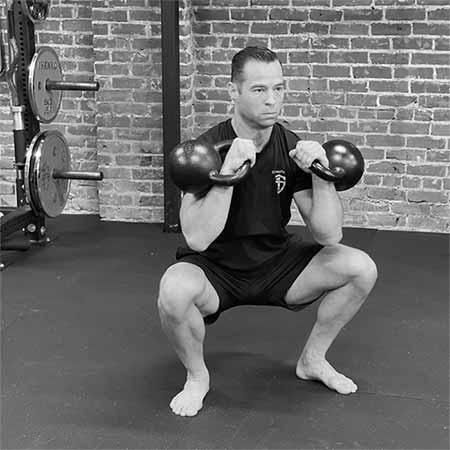 Tony Gracia mentre esegue il double kettlebell front squat